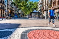 Man wearing a surgical mask walking in a deserted Rambla street, Barcelona, Catalonia, Spain
