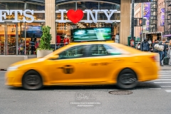 I Love New York gift shop sign and blurred yellow taxi cab passing, Times Square, New York, USA