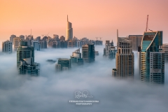 Foggy sunrise with Dubai Marina's skyscrapers towering over the low clouds, Dubai, United Arab Emirates